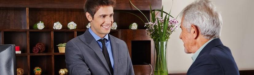 Lächelnder Rezeptionist im Hotel gibt einem Senior seine Schlüsselkarte